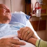 Old man lying in hospital bed holding daugher's hand