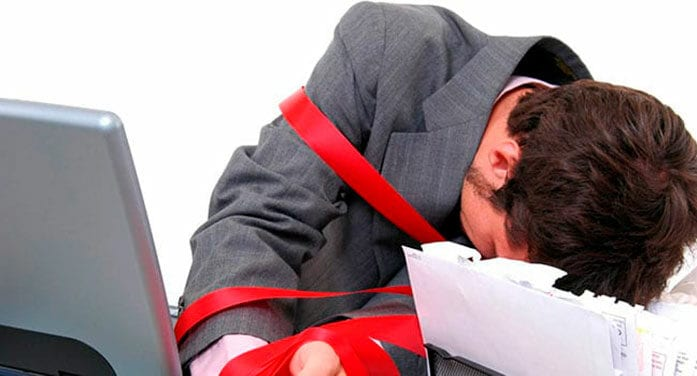 Businessman wrapped in red tape
